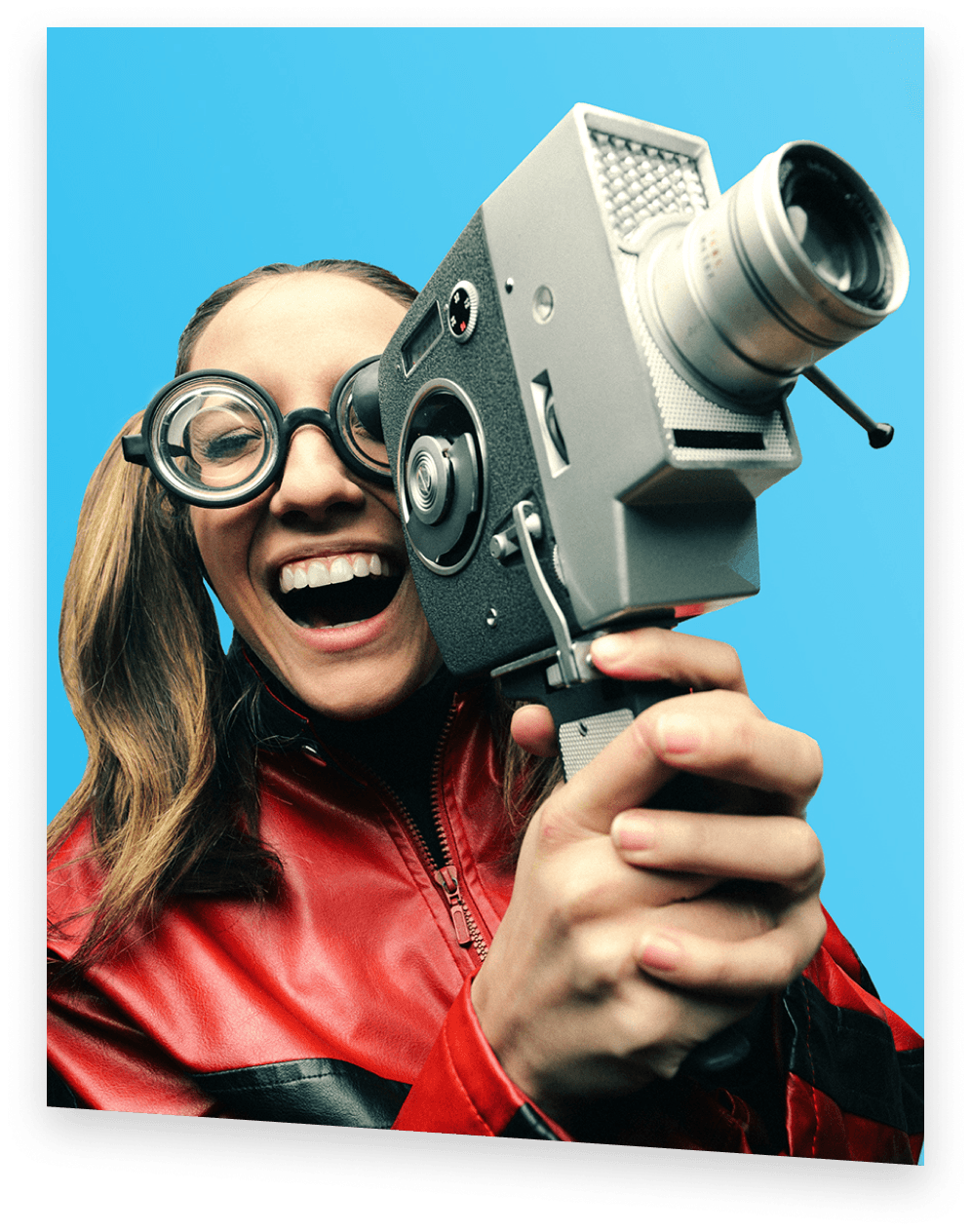 A smiling shmoop student wearing big glasses holding up a camcorder to her eye