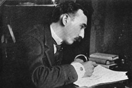 Man with mustache writing on a piece of paper